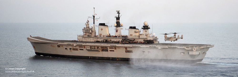 Image courtesy of UK Ministry of Defence is of a US Marine Corps MV-22B Osprey Aircraft from the USS Kearsarge, lands onboard HMS Illustrious during Cougar 13.